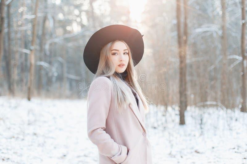 Härlig stilfull ung flicka i en trendigt svart hatt och lag royaltyfri bild