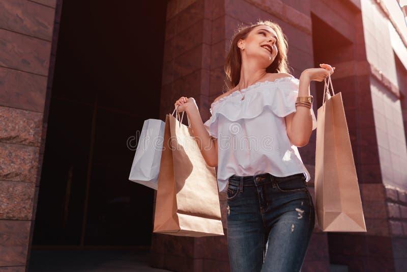 Härlig stilfull ung kvinna med shoppingpåsar som går på stadsgatan i sommar Lycklig och upphetsad flickashoppare försäljning royaltyfri foto