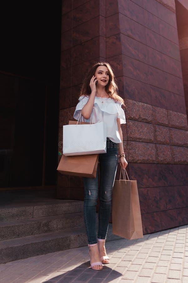 Härlig stilfull ung kvinna med shoppingpåsar som går ut ur galleria på stadsgatan och talar på telefonen royaltyfri fotografi