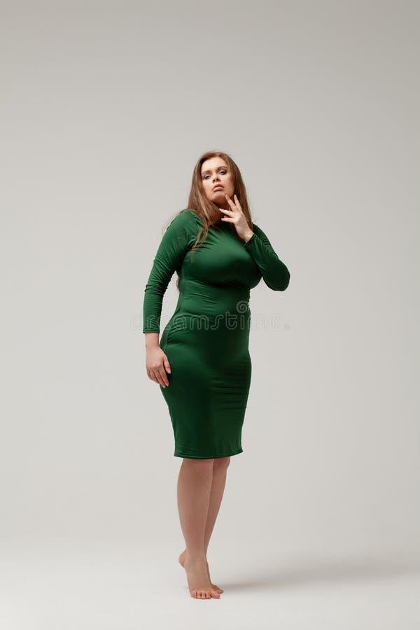 Härlig stor flicka i grön klänning royaltyfria foton
