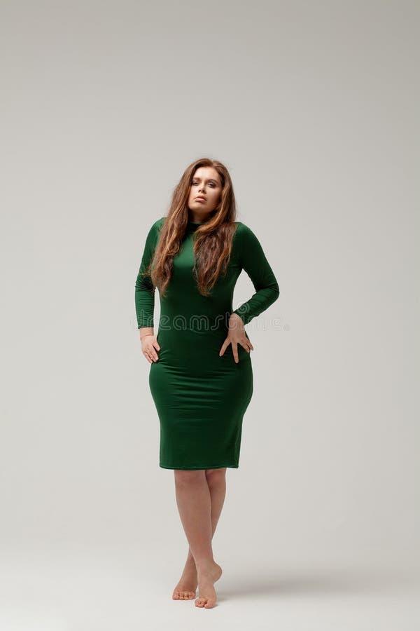 Härlig stor flicka i grön klänning royaltyfri foto