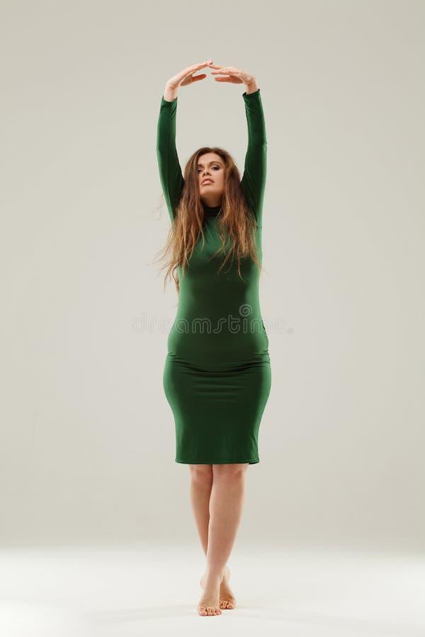 Härlig stor flicka i grön klänning royaltyfri bild
