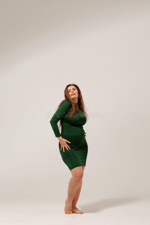 Härlig stor flicka i grön klänning arkivbild