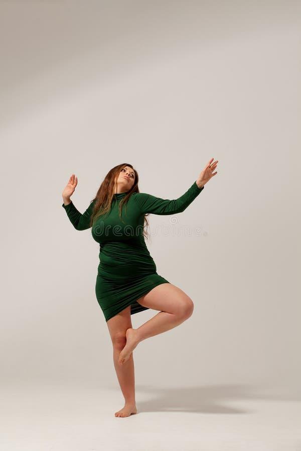 Härlig stor flicka i grön klänning royaltyfri fotografi