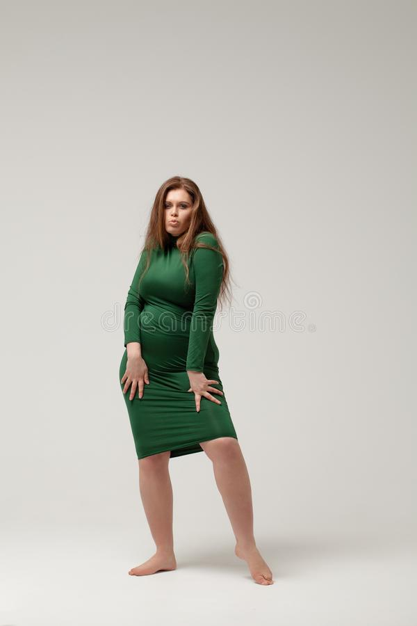 Härlig stor flicka som isoleras i grön klänning royaltyfria foton
