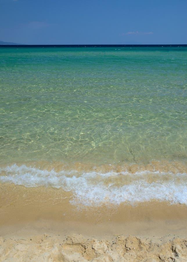 Härlig strandbakgrund, klart vatten och sand royaltyfria foton