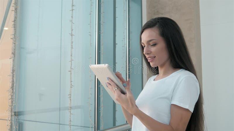 Härlig student för ung kvinna som använder hennes vita minnestavla i shoppinggallerian, lyckligt universitetliv royaltyfria foton