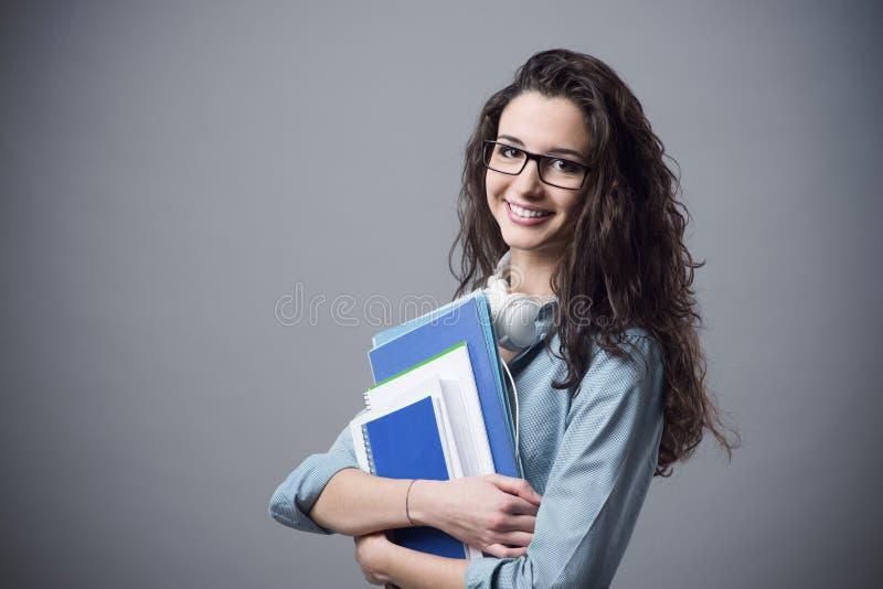 Härlig studentflicka som poserar med anteckningsböcker arkivfoton
