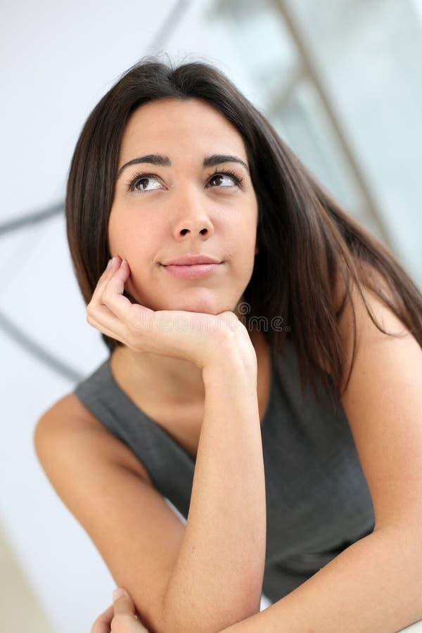 Härlig studentkvinna som är fundersam royaltyfri fotografi