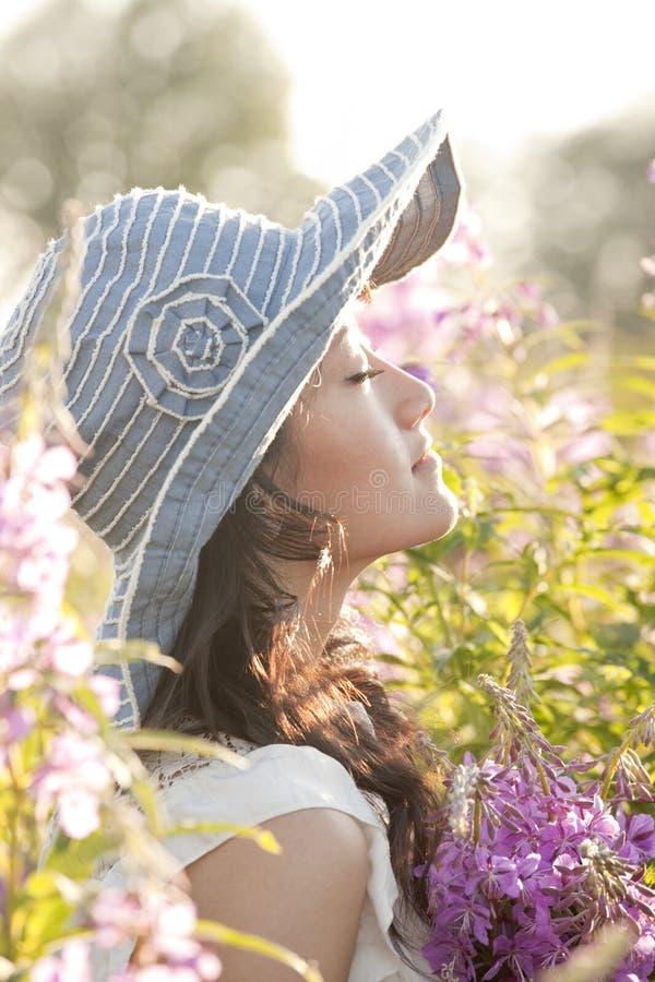 Härlig, sund, sinnlig, sexig ung asiatisk kvinna som tycker om sommarsolljus i en blommaträdgård Hon bär en solhatt arkivbilder