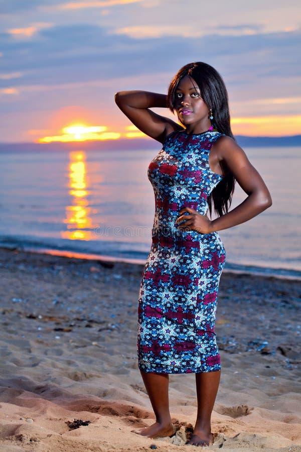 Härlig svart afrikansk amerikankvinna som poserar på stranden på su royaltyfri fotografi
