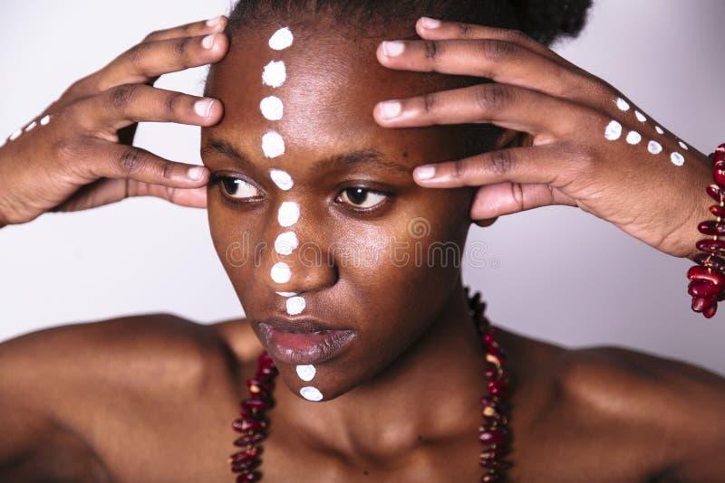 Härlig svart flicka med facearttouchs hennes framsida royaltyfri fotografi