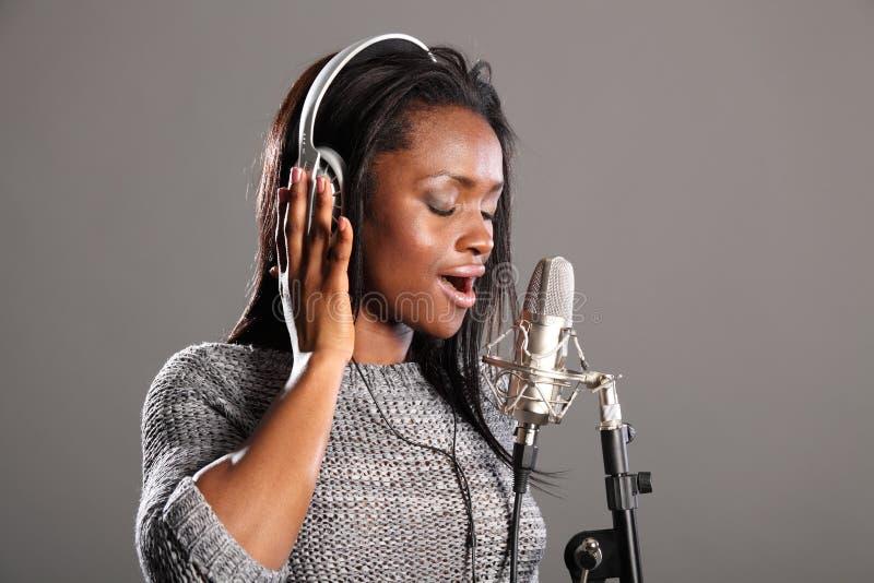 härlig svart görande mic-musik sjungande kvinna royaltyfria foton