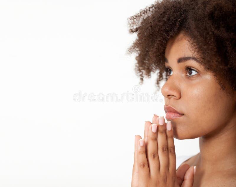 Härlig svart kvinna för stående som tillsammans ber, ung flicka med henne händer, closeuputtryck Religiontro och royaltyfri foto