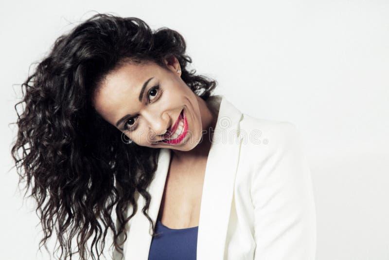 Härlig svart kvinna med långt hår som ler, emitions Röd läppstift royaltyfri fotografi