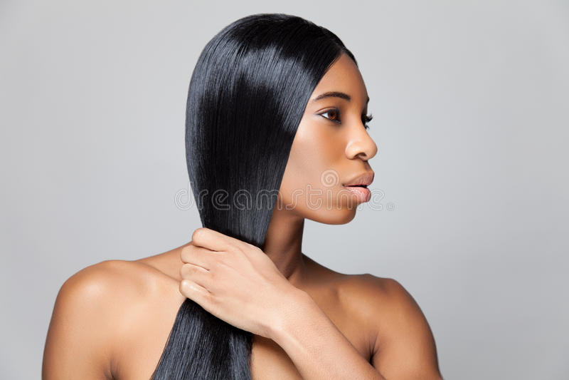 Härlig svart kvinna med långt rakt hår royaltyfri bild