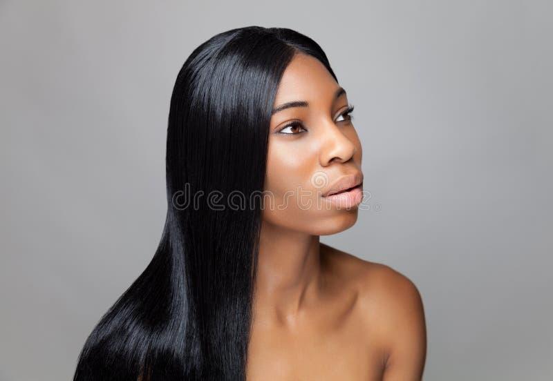 Härlig svart kvinna med långt rakt hår royaltyfri fotografi