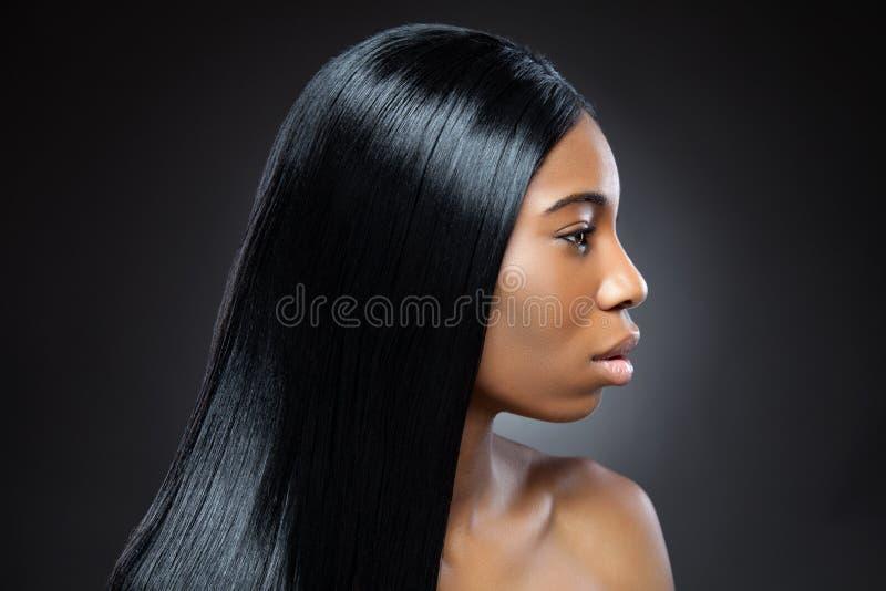 Härlig svart kvinna med långt rakt hår arkivbild