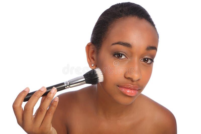 Härlig svart kvinna som använder sminkpulverborsten royaltyfri bild