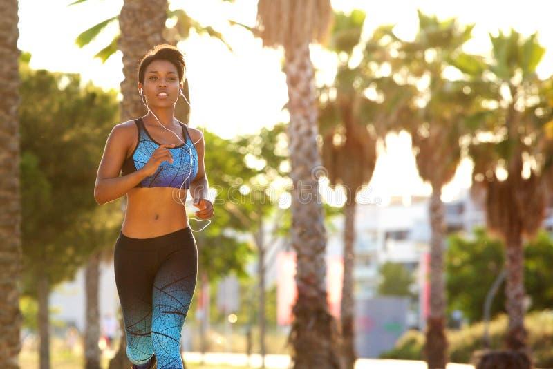Härlig svart kvinnaspring med hörlurar royaltyfri bild