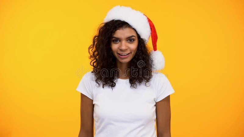 Härlig svart kvinnlig i den santa hatten som ser kameran på ljus bakgrund, parti arkivbild