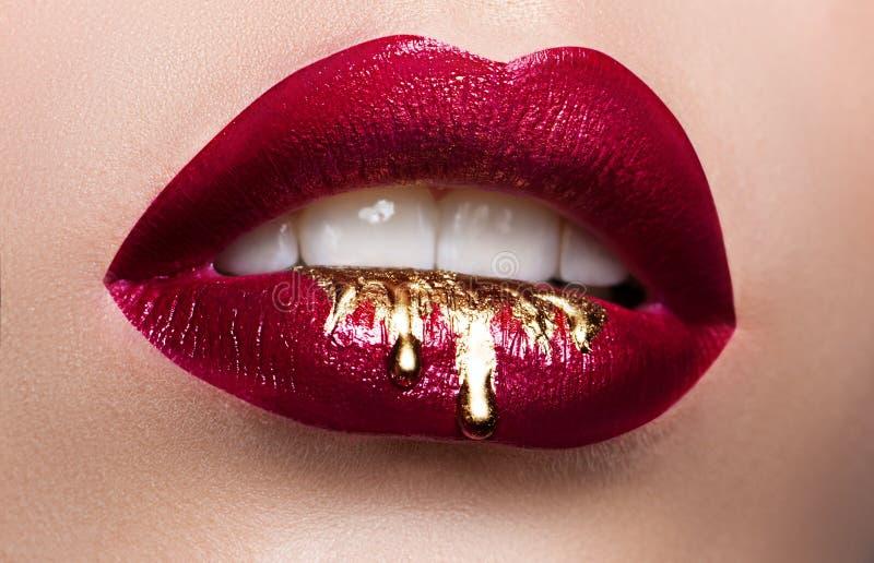 härlig svart läppstift för closeupkvinnligkanter Röd läppstift, guld- målarfärg som flödar över hans kanter Se mina andra arbeten arkivfoton