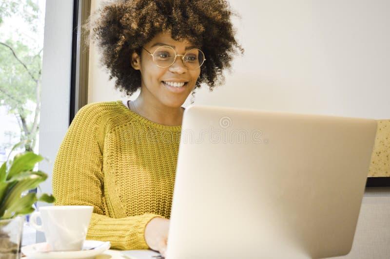 Härlig svart studentkvinna som ler på bärbara datorn som dricker kaffe arkivfoto