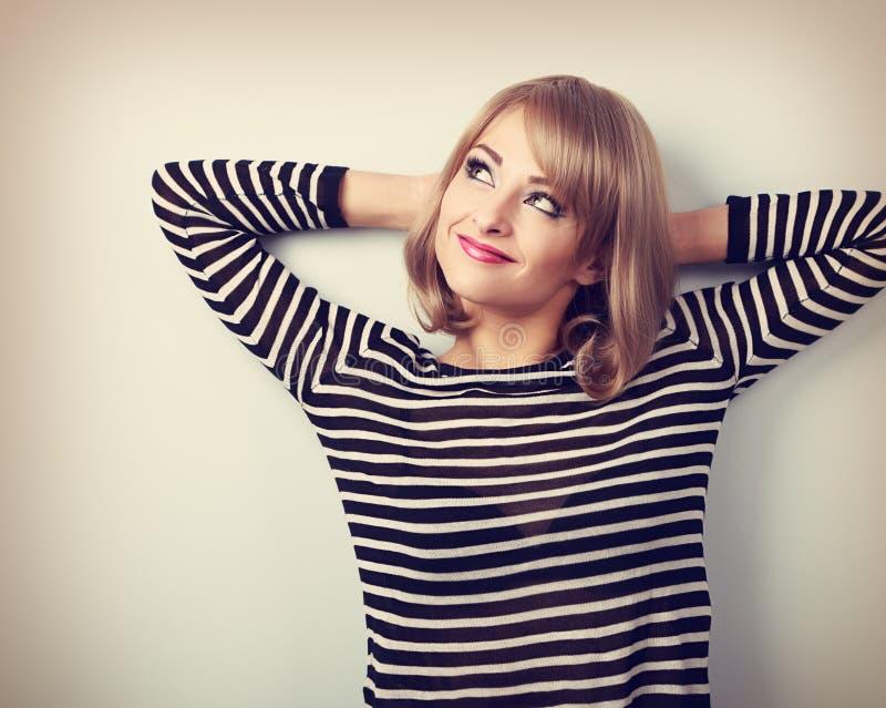 Härlig tänkande blond ung kvinna i tröjan som ser upp signal arkivbild