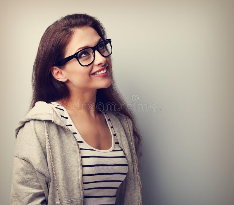 Härlig tänkande ung kvinna i exponeringsglas som ser upp Tappning po arkivbilder