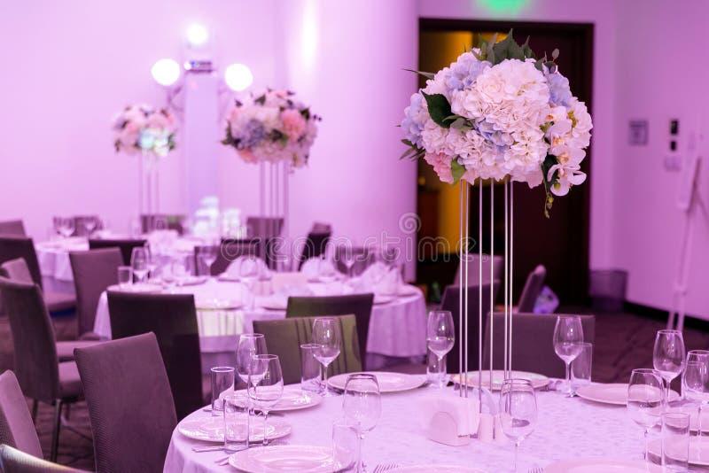 Härlig tabellinställning med ordningar för lerkärl och för vit blomma i en vas på en hög stam för ett parti, ett bröllopmottagand arkivbild