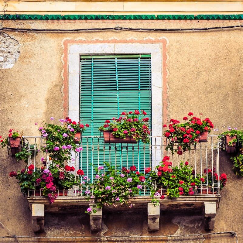 Härlig tappningbalkong med färgrika blommor och dörren arkivbild