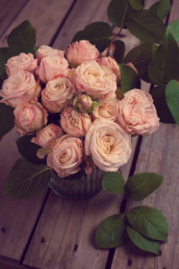Härlig tappningbukett av nya rosor på träbräde royaltyfri foto