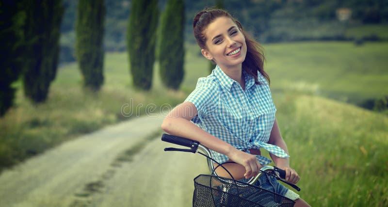 Härlig tappningflicka som sitter bredvid cykeln, sommartid arkivbilder