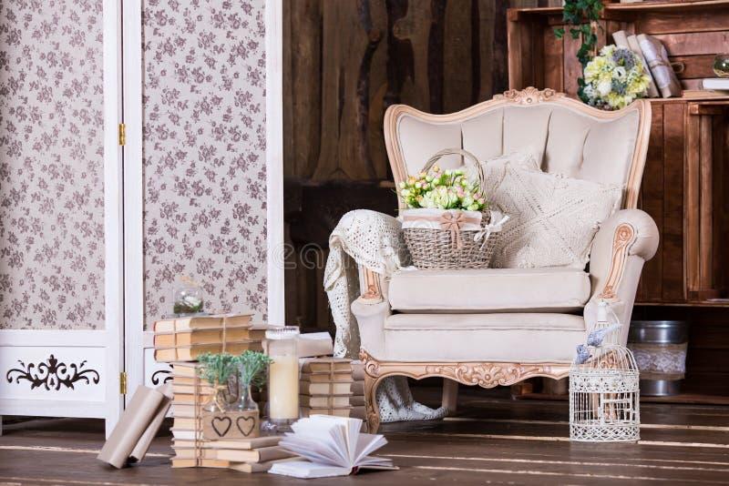 Härlig tappninginre med gamla stol- och bokhögar royaltyfria bilder