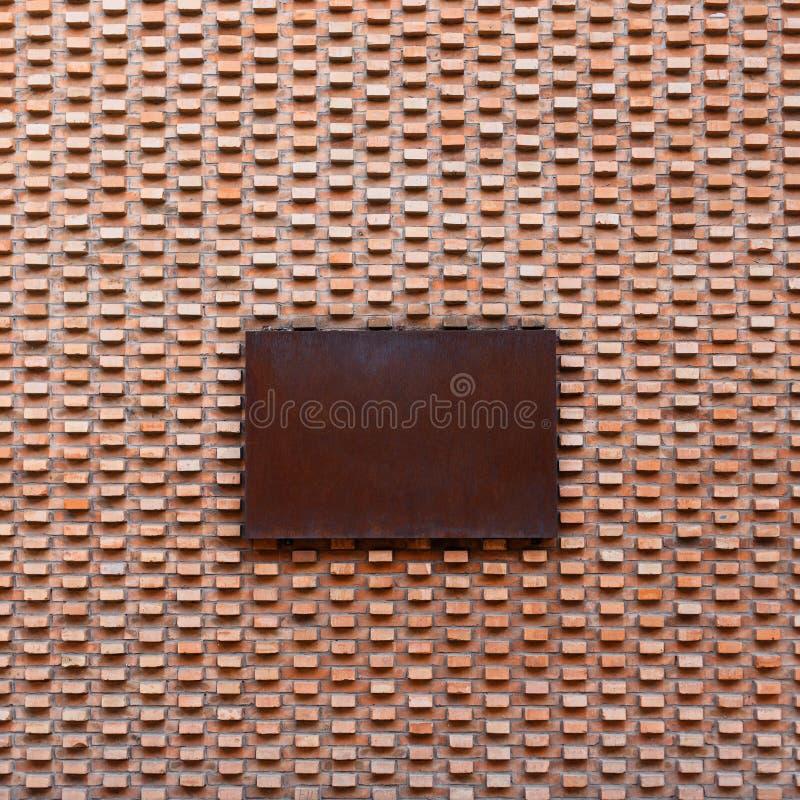 Härlig tappningtegelstenvägg med det rostiga metalltecknet royaltyfri bild