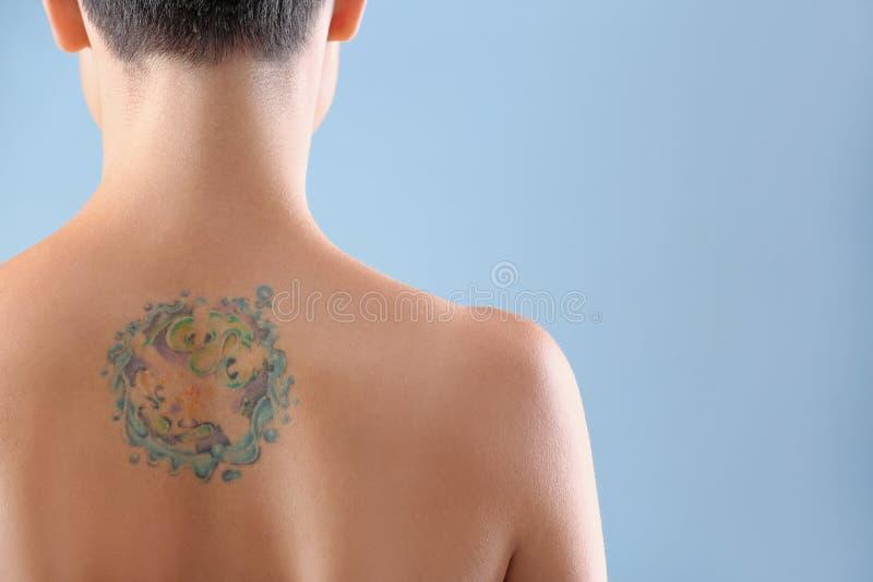 Härlig tatuering på kvinnligbaksida mot färgbakgrund arkivfoton
