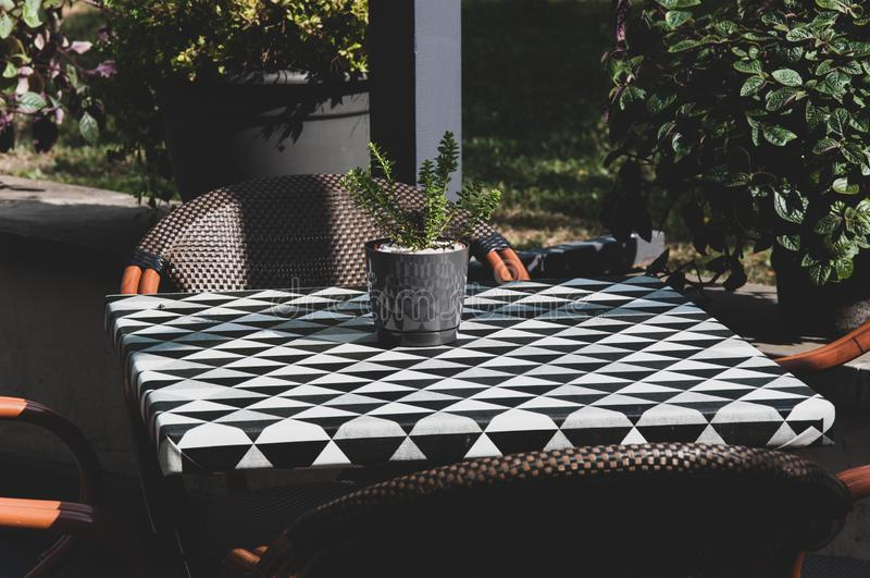 Härlig terrass, balkong, med blomkrukan på den lilla checky tabellen och trästolar tonad bild royaltyfri fotografi