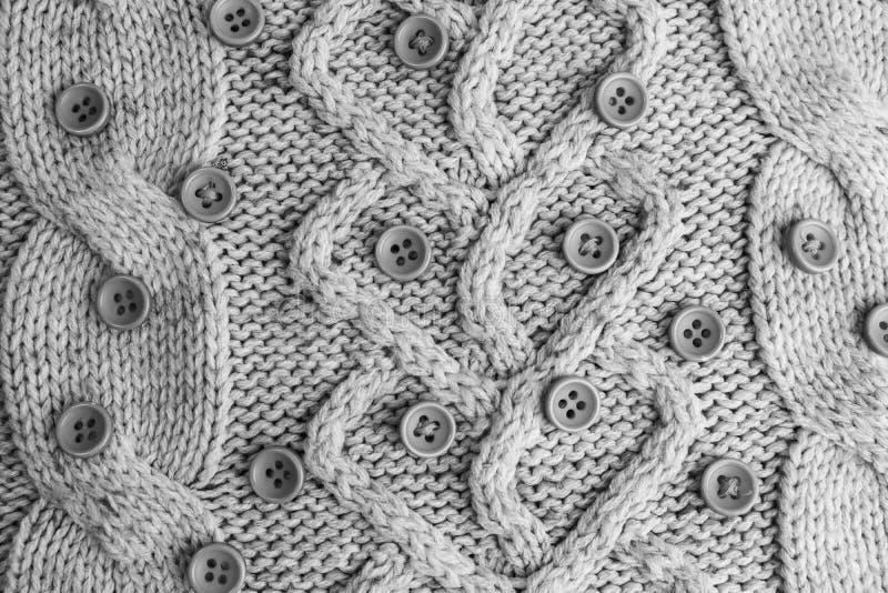Härlig textur av en mjuk varm naturlig tröja med en stucken modell av garn och svartvita små runda knappar arkivbild