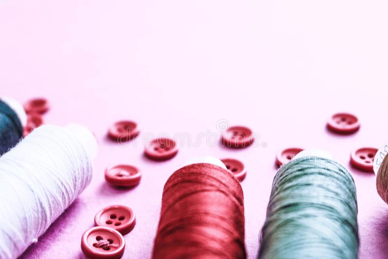 Härlig textur med massor av runda röda knappar för att sy, handarbete och skeins av rullar av tråden kopiera avstånd Lekmanna- lä arkivfoto