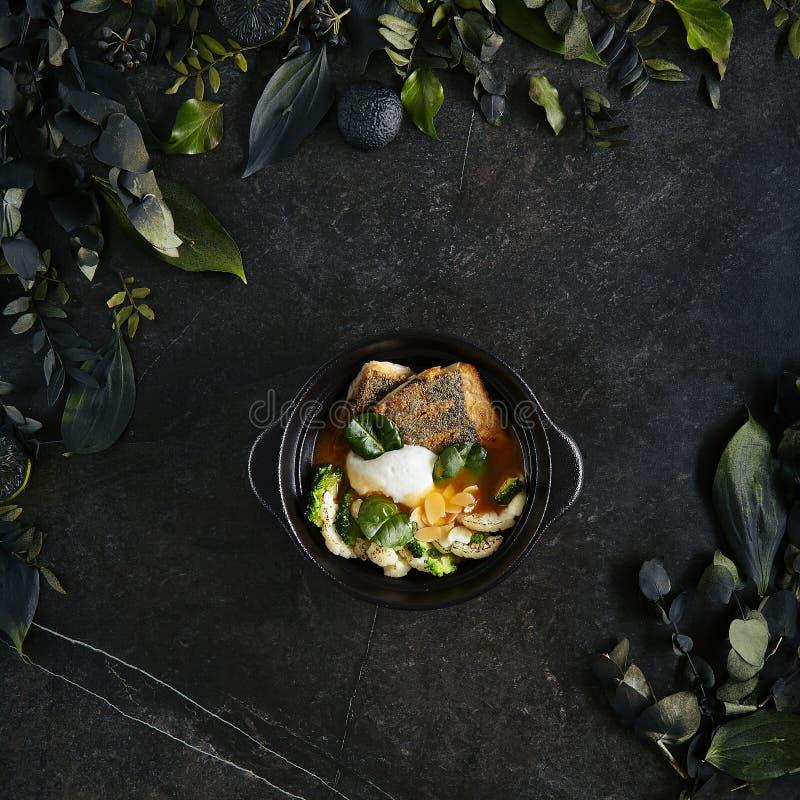 Härlig tjänande som Branzino eller Seabassfilé med bästa sikt för för Bisquesås och spenat royaltyfri bild