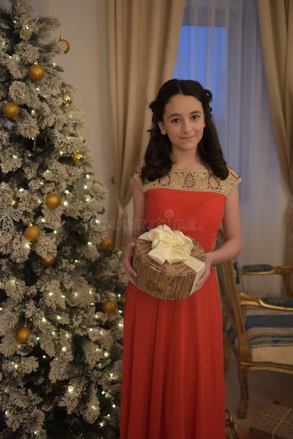 Härlig tonårig flicka i den smarta röda klänningen arkivfoto