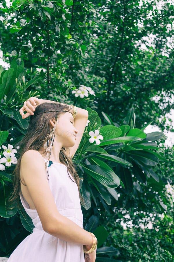 Härlig tonårig flicka i den vita klänningöverkanten med plumeriaträdet Boho stilstående royaltyfri fotografi