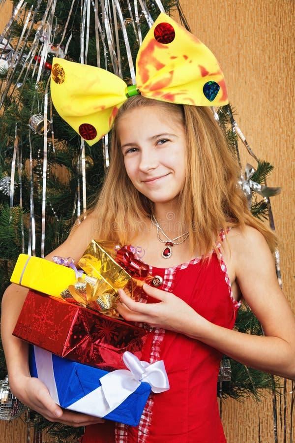 Härlig tonårig flicka i hållande gåvaaskar för rolig dräkt royaltyfri foto