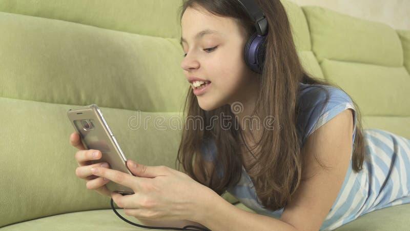 Härlig tonårig flicka i hörlurar som sjunger karaokesånger i smartphone royaltyfri foto