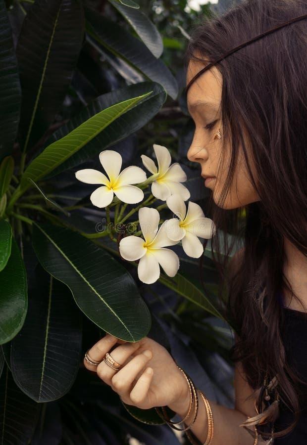 Härlig tonårig flicka i svart ärmlös tröja med plumeriaträdet Boho stilstående royaltyfria bilder