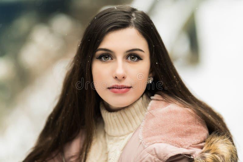 Härlig tonårig flicka med den långa bruna hårståenden utanför med snö royaltyfri bild
