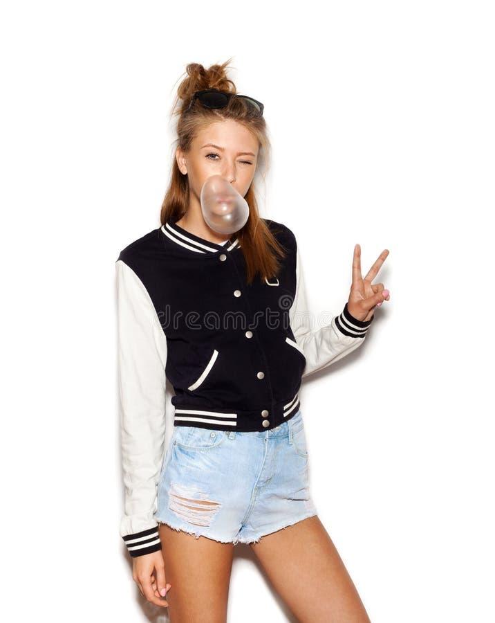 Härlig tonårig flicka som blåser upp bubblan av tuggummi modern modeflicka arkivbild