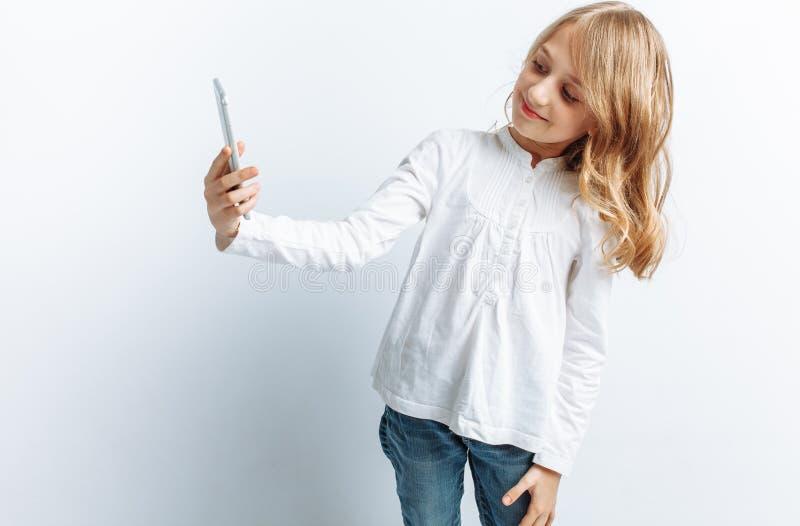 Härlig tonårig flicka som gör selfie på telefonen, fotostudio som isoleras arkivbild