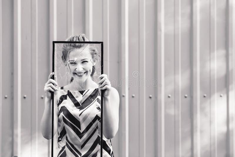 Härlig tonårig flicka som rymmer brutet exponeringsglas i hennes händer Begreppsfeminism fotografering för bildbyråer