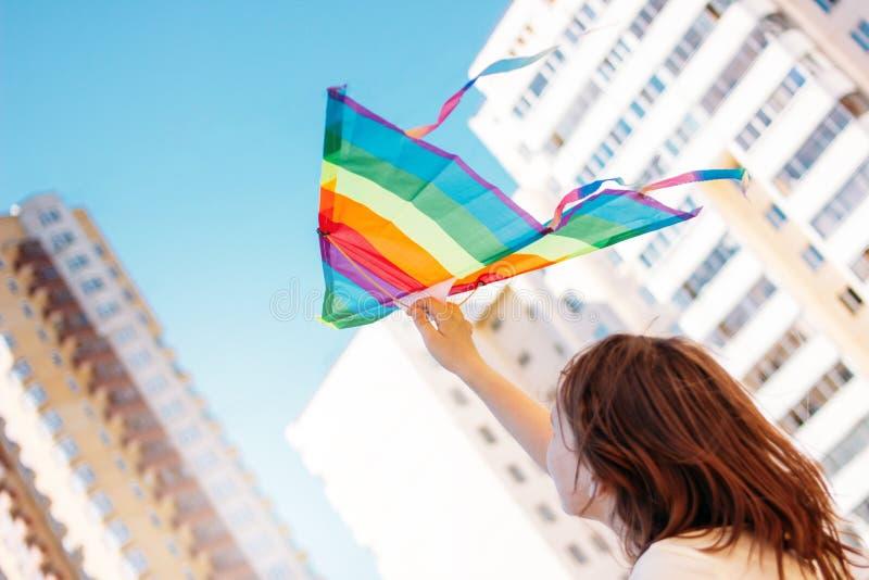 H?rlig ton?rig flicka som rymmer den pappers- draken och att tycka om sommarsemestrar i stad royaltyfri fotografi